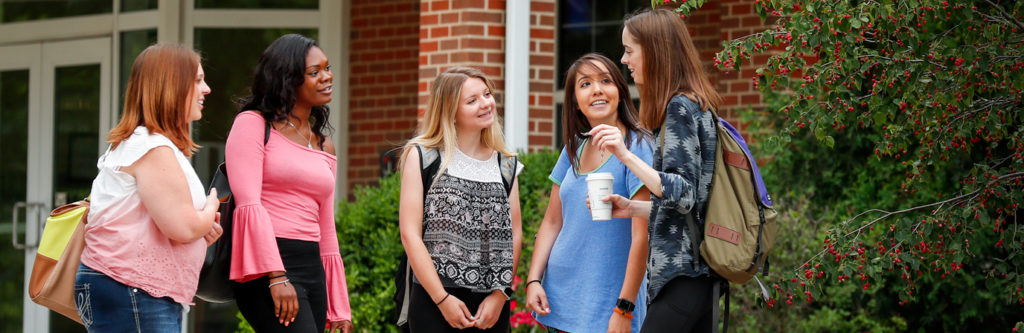 Graduate students catch up after class as part of their graduate school experience.