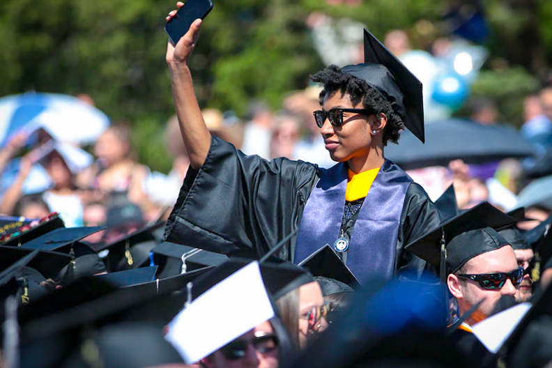 graduate waving in cap and gown