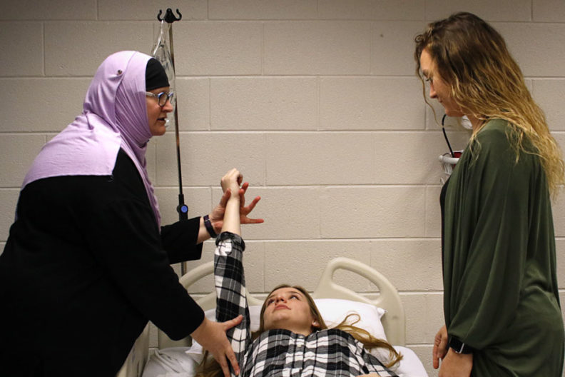 An occupational therapy instructor demonstrates on a patient in a classroom setting at Elmhurst University.