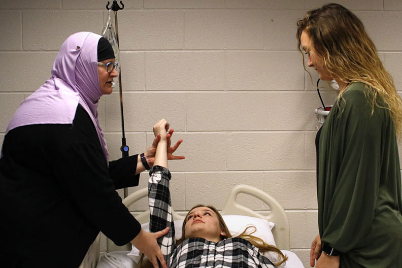 An occupational therapy instructor demonstrates on a patient in a classroom setting at Elmhurst College.