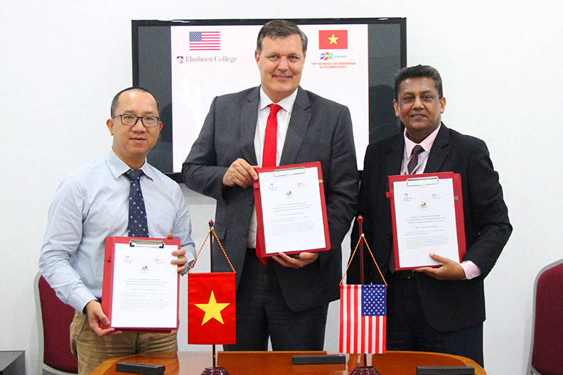 Elmhurst College President Troy D. VanAken, center, holds a signed agreement with officials from Vietnam's FPT School of Business and Technology.