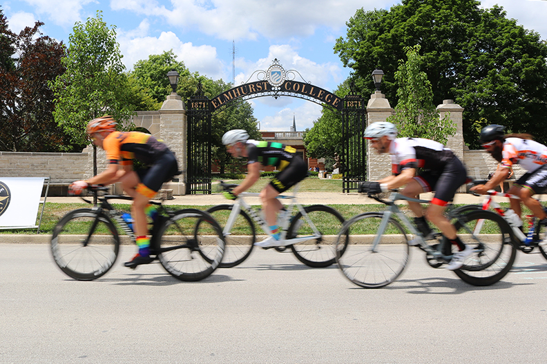 Cyclists ride past Elmhurst College's campus during the annual cycling classic.