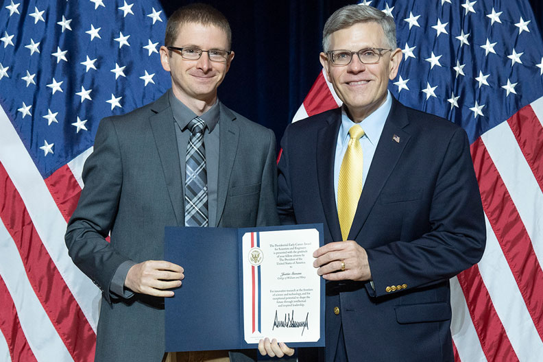 Elmhurst College alumnus Justin Stevens is presented the Presidential Early Career Award for Scientists and Engineers by White House official Kelvin Droegemeier.