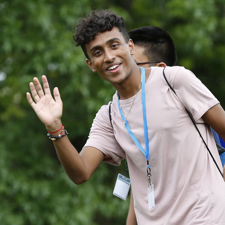 A new Elmhurst College student smiles and waves for the camera during move-in day 2019.