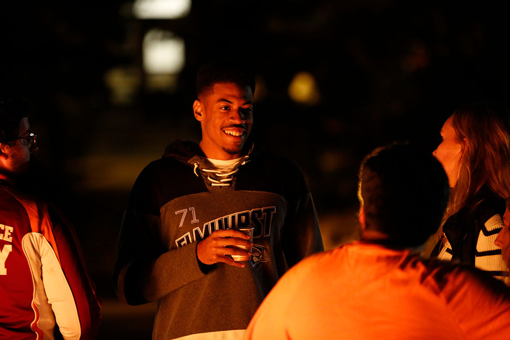 Will Lyles socializes with friends at Elmhurst College's 2019 Homecoming bonfire and pep rally.