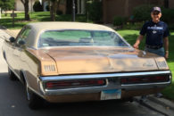 Elmhurst College alumnus Keith Reed stands next to the 1970 Dodge Monaco he used to commute to school every day as a student.