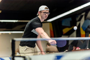 A student plays ping-pong in the Bluejay Roost, a hangout for students inside Elmhurst College's Frick Center.