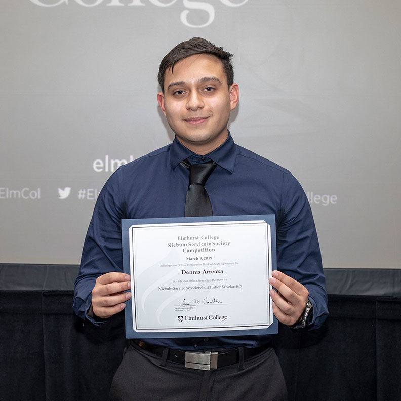 Dennis Arreaza stands with his certificate of award for Elmhurst College's 2019 Niebuhr Service to Society scholarship competition.
