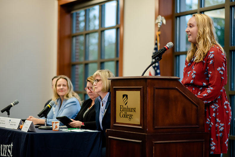 A student speaks at the podium while panelists look on during the Elmhurst College Master's Entry in Nursing Practice Legislative Breakfast in October of 2019.