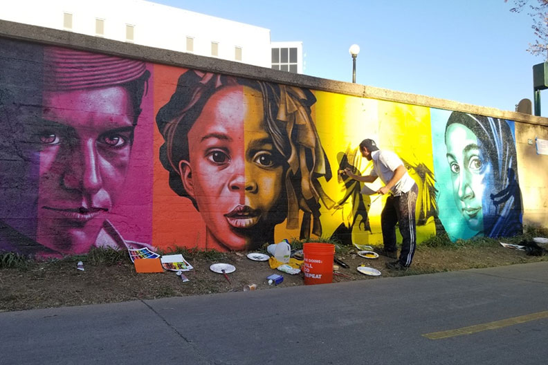 "Artist and Elmhurst College faculty member Rafael Blanco is shown painting ""Color Isn't Race,"" his mural in Denver, Colorado."