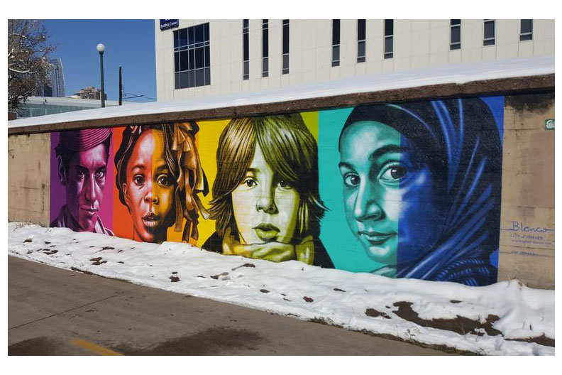 """Color Isn't Race,"" a public mural in Denver, Colorado, featuring four diverse people shaded in different colors by artist and Elmhurst College faculty member Rafael Blanco."