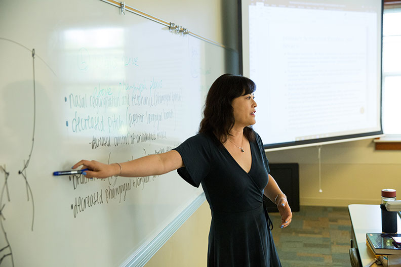 A professor points to writing on a whiteboard while teaching a class at Elmhurst College.