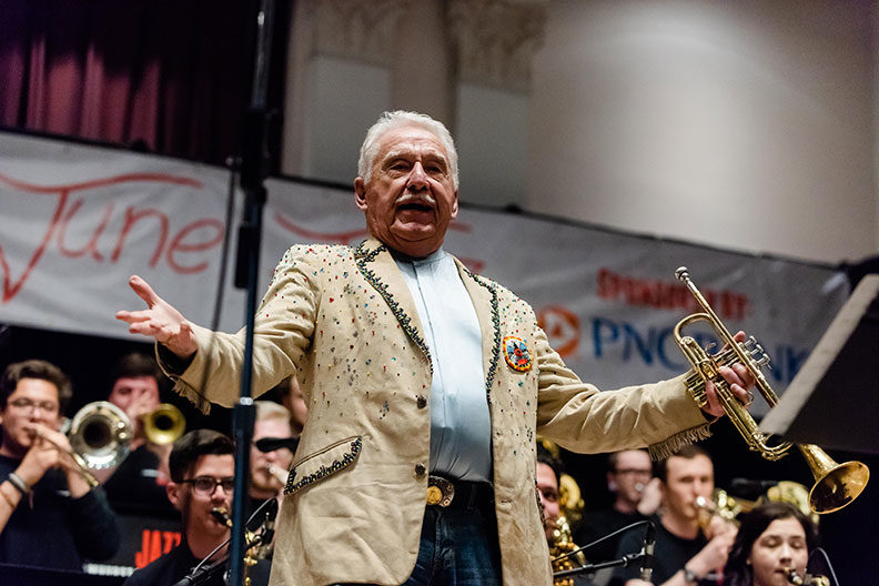 Doc Severinson greets the audience with arms outspread during the Elmhurst College June Jazz event in 2019.