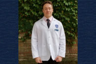 Photo of Elmhurst College student Nicholas Bank getting his white coat at Case Western Reserve University School of Medicine.