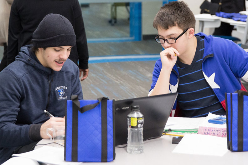 Two Elmhurst College students focus on a laptop while studying in the Learning Center within the A.C. Buehler Library.