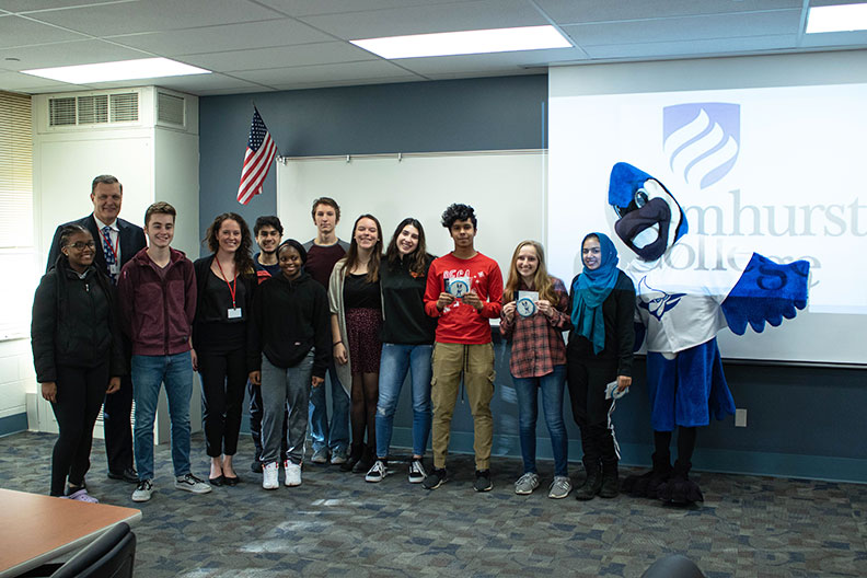 A group of Willowbrook High School students poses with Elmhurst College president Troy VanAken and mascot Victor E. Bluejay at a special welcome event.