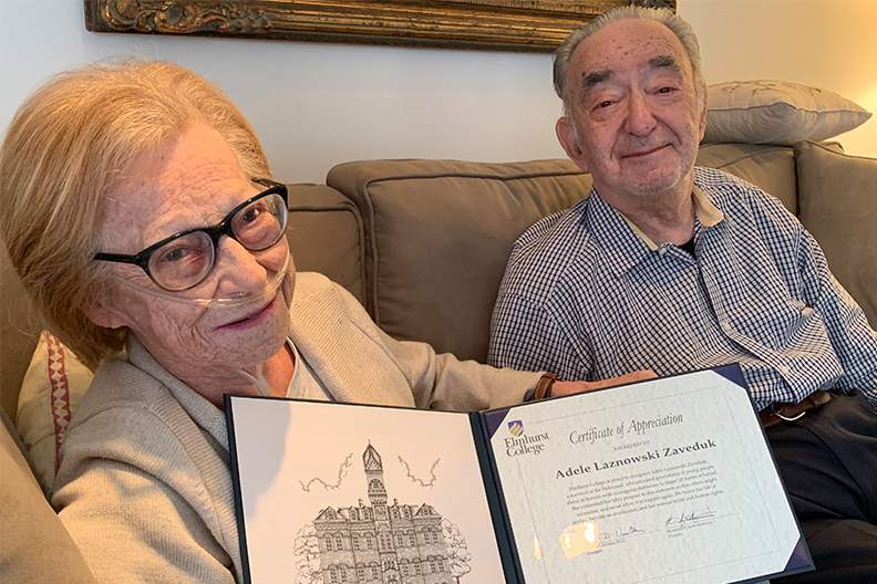 Adele Laznowski Zaveduk and her husband, Ben Zaveduk, sitting on a couch with her certificate of appreciation.