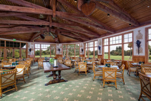 A photo of tables set up inside a dining area in the Hole in the Wall Golf Club in Naples, Florida.