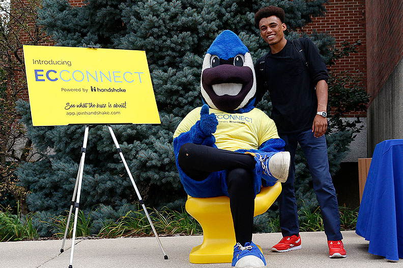 Elmhurst College mascot Victor E. Bluejay, seated in a yellow chair, poses with a student during a career center event.