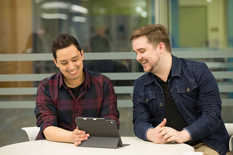 Two Elmhurst College students look at a tablet screen in the College's library and share a laugh.