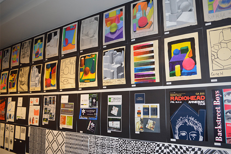 A wall filled with art work from local high schools.