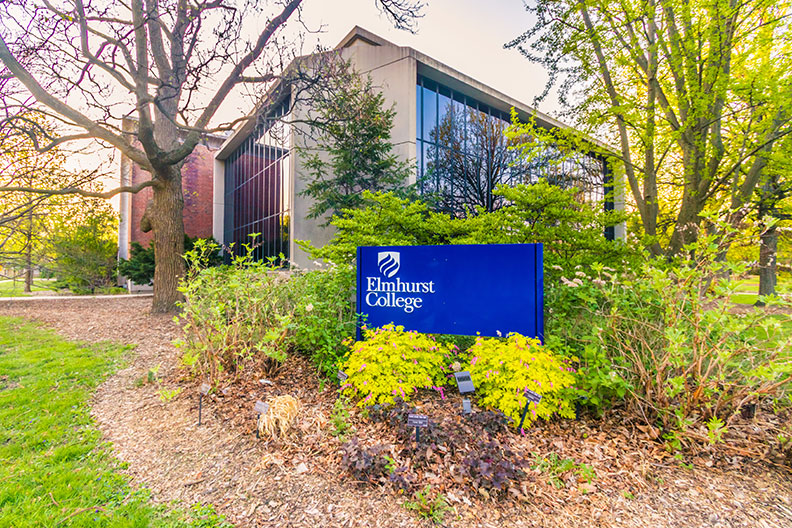 """A photo of the exterior of the Schaible Science Center on the campus of Elmhurst College. A blue sign that says """"Elmhurst College"""" is in the foreground."""