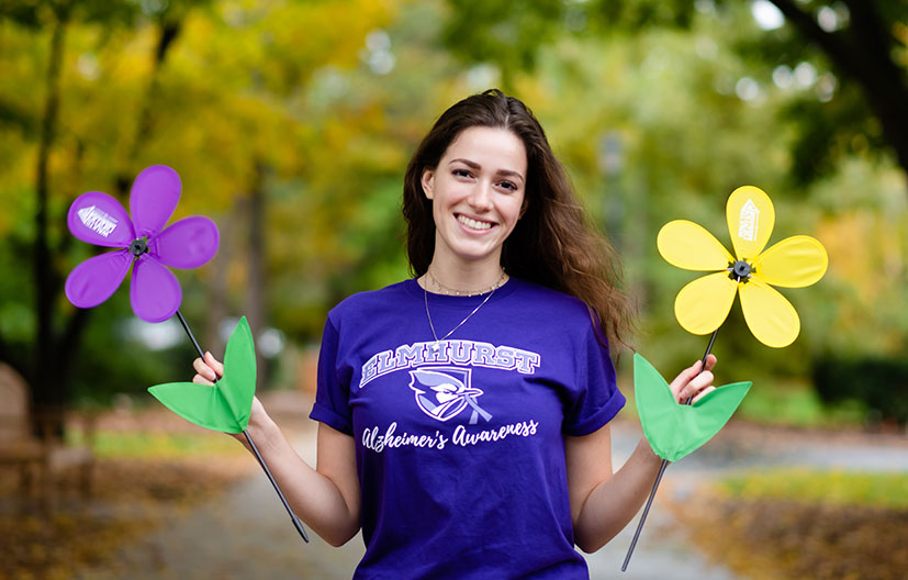 A female Elmhurst College student holds a colorful flower in each hand to promote Alzheimer's awareness month.