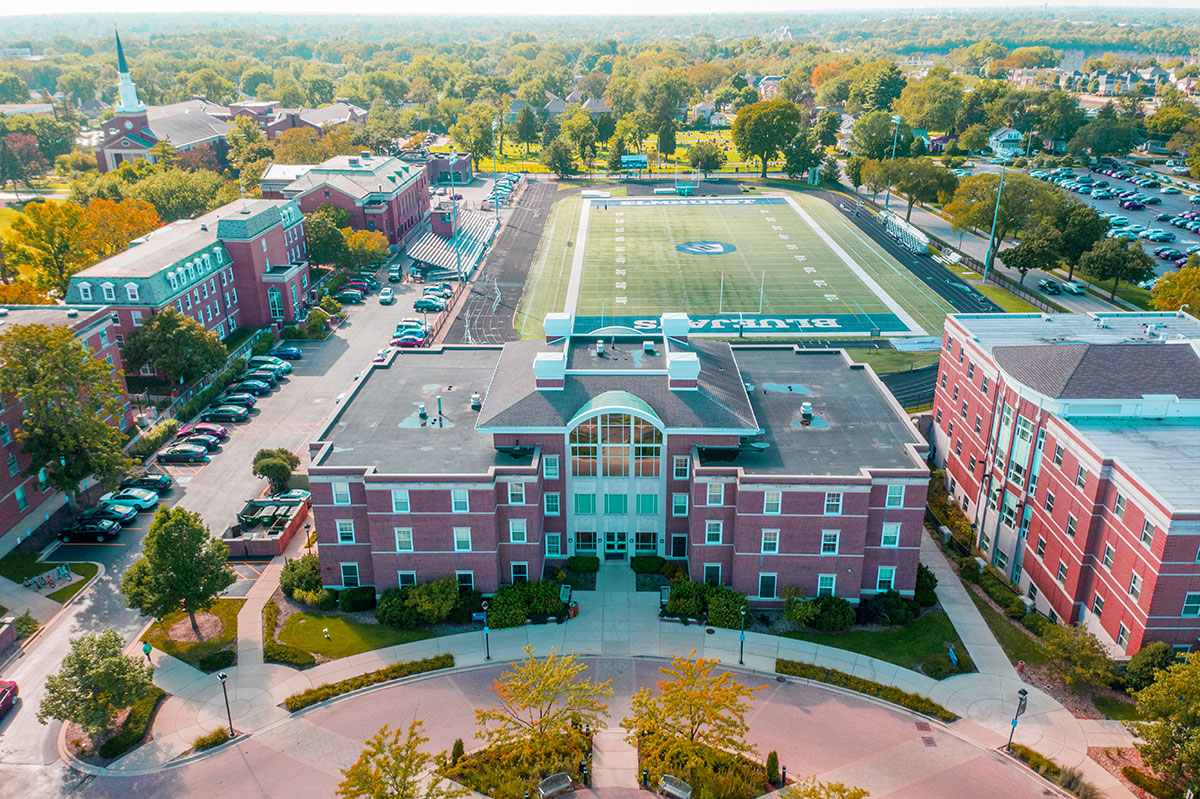 Circle Hall is in the foreground of an aerial photograph of the Elmhurst College campus, with Langhorst Field in the background.