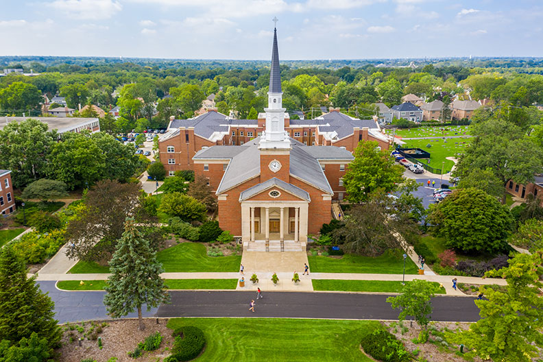 An aerial photograph of the Elmhurst College campus shows Hammerschmidt Memorial Chapel.