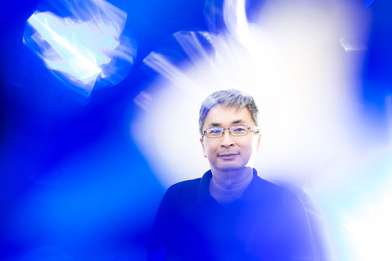 A portrait photograph of Siaw-Peng Wan, an Elmhurst College professor of business administration. A blue blur effect is in the foreground.