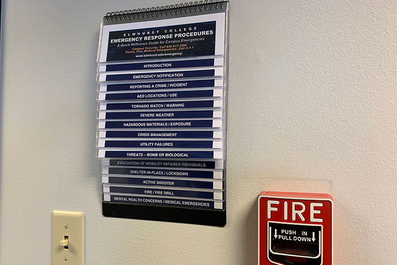 An emergency response procedures flip chart hangs in the hallway of a building on Elmhurst College's campus.