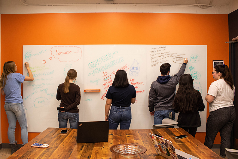 Six Elmhurst College students draw and write together on a large whiteboard in a classroom. Elmhurst is promoting entrepreneurship with a new initiative on campus.