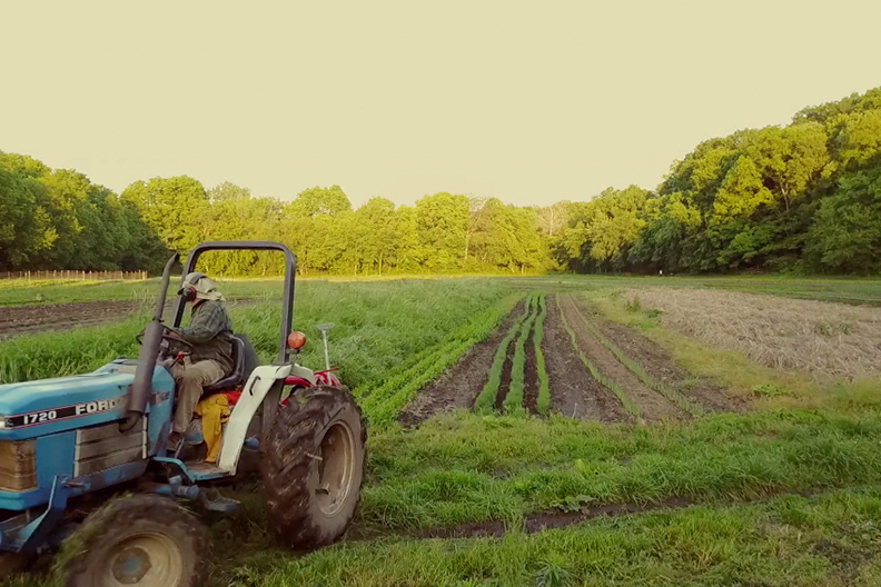 A still from 'Seasons of Change on Henry's Farm' of a blue tractor farming land.
