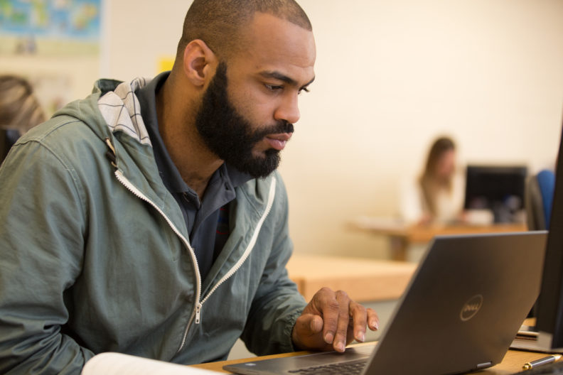 A graduate student works on his laptop during class. Elmhurst College will host a virtual information session for its graduate programs in April.