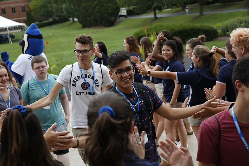 A crowd of Elmhurst University students welcomes new first-year and transfer students to campus with high-fives and handshakes.