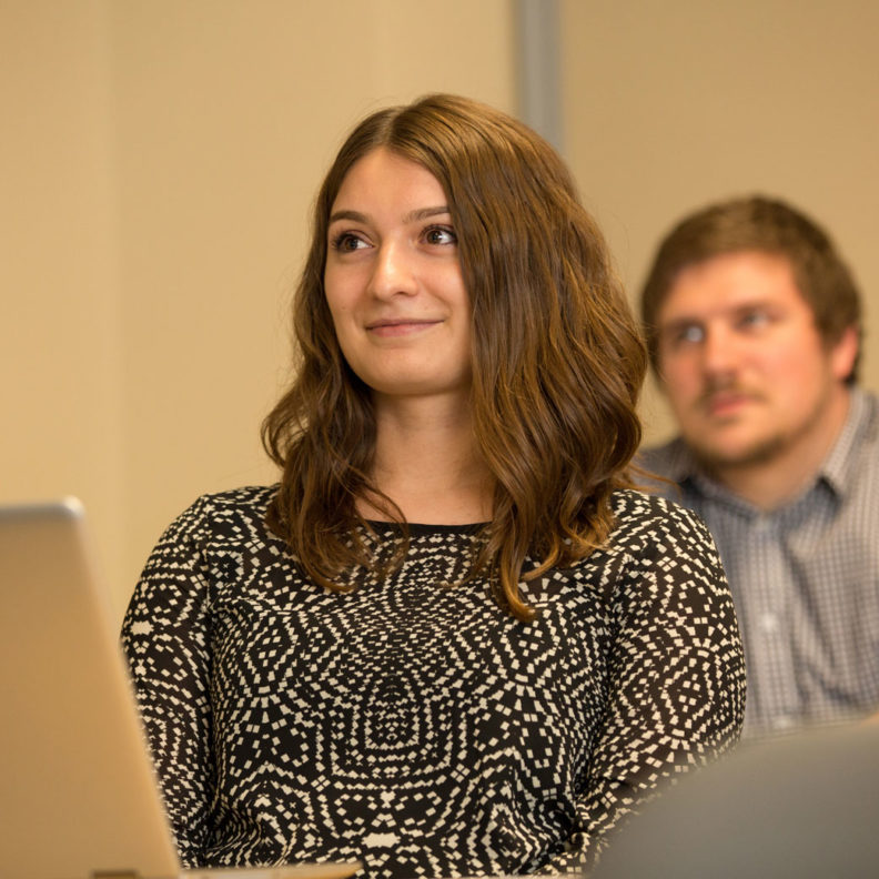A female student, with a male classmate in the background, listens to a lecture during a marketing research graduate-level course at Elmhurst University.