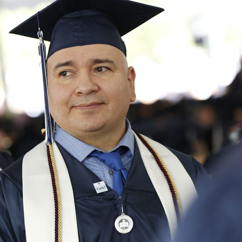 A student stands during Elmhurst University's 2019 undergraduate Commencement ceremony.