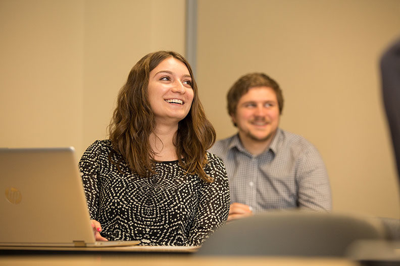 A female and male Elmhurst University graduate student smile during a market research class.