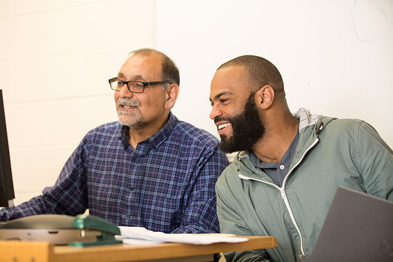 An Elmhurst University graduate student in Computer Information Technology laughs while Prof. Ali Ghane points to a computer screen.