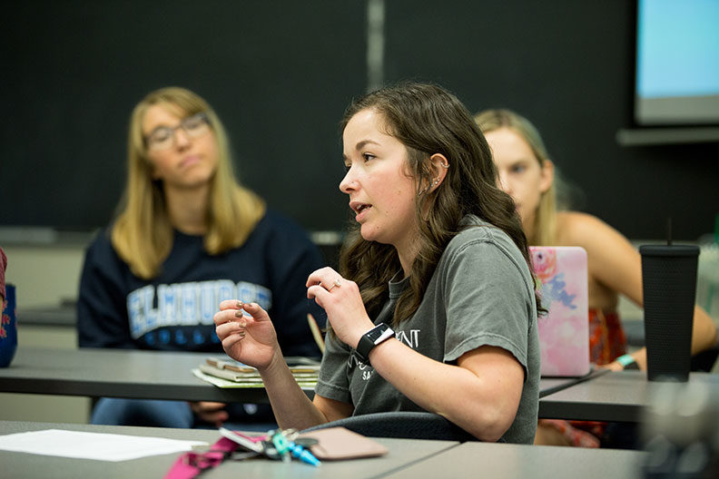 A female Elmhurst University graduate student in Industrial/Organizational Psychology speaks during class while two classmates look on.