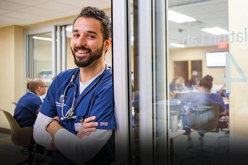 A male Elmhurst University graduate student in nursing leans against a glass door.