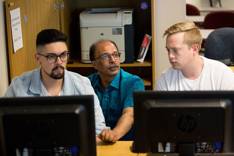 Two Elmhurst University graduate students in supply chain management sit behind computer monitors while Prof. Roby Thomas kneels behind them in a discussion.