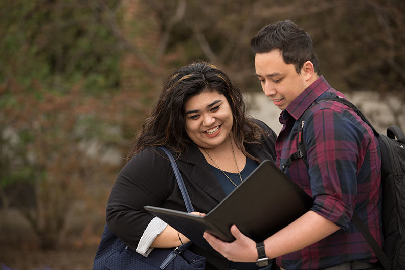 Two Elmhurst University graduate students look down at an open portfolio that one of the students is holding.