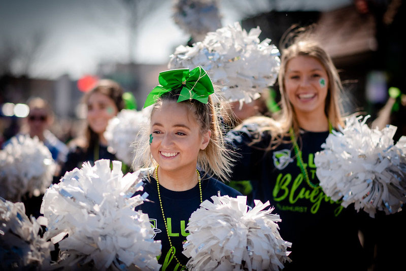 Elmhurst University cheerleaders holding white poms march in the City of Elmhurst Illinois' annual St. Patrick's Day parade.