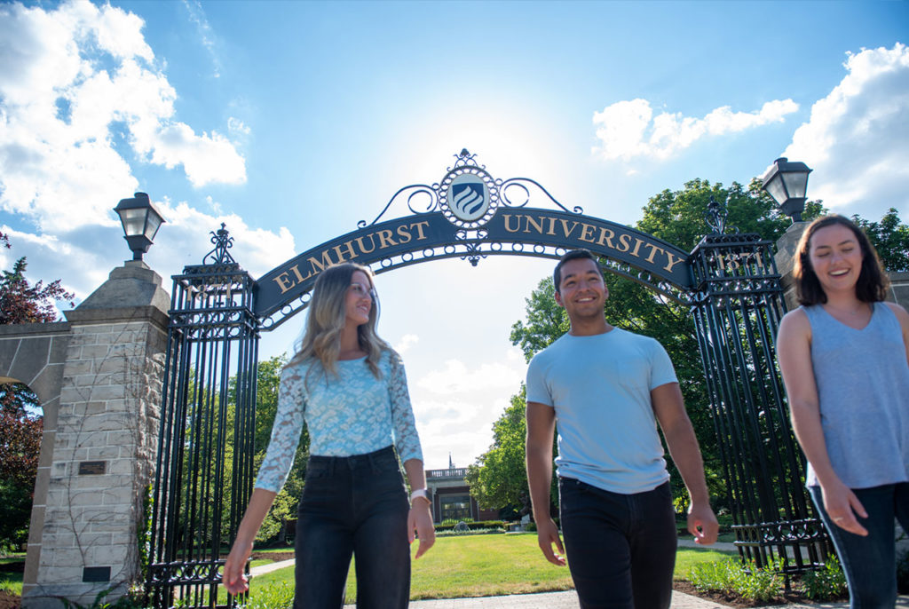 A female student and a male student at Elmhurst University walk beneath the Gates of Knowledge on campus.