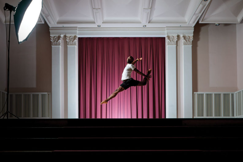Elmhurst University student Brandon Lee performs a dance leaps on stage in the Hammerschmidt Memorial Chapel.
