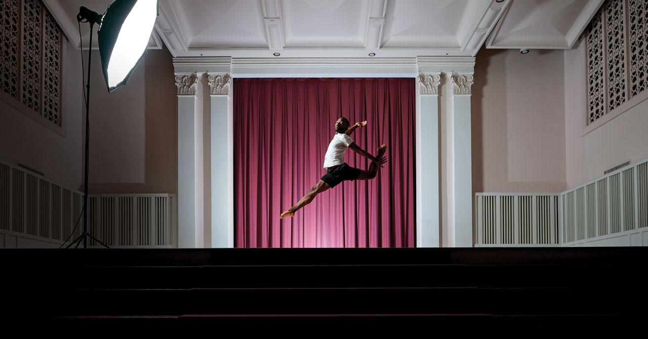 Elmhurst University student Brandon Lee performs a dance leaps on stage in the Hammerschmidt Memorial Chapel.