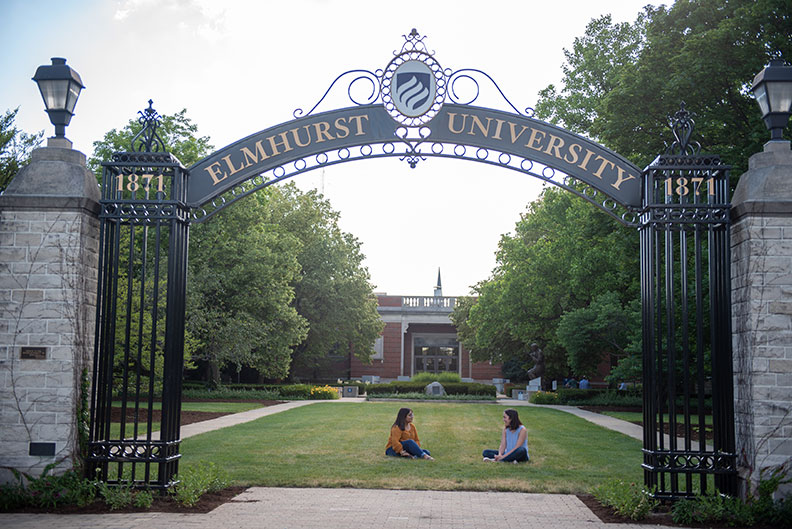 Two students sit on the grass beneath the Elmhurst University Gates of Knowledge.