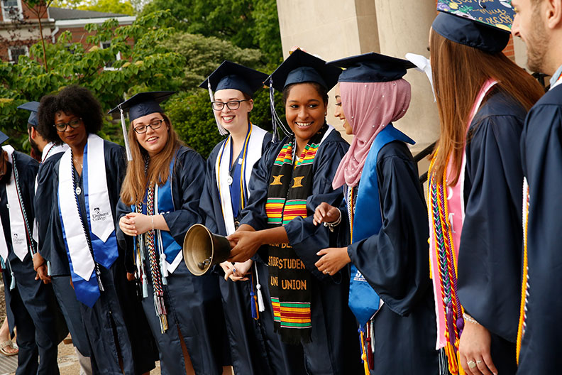 A diverse group of honor graduates stand together and ring a ceremonial bell during Elmhurst University's 2019 Commencement ceremony.