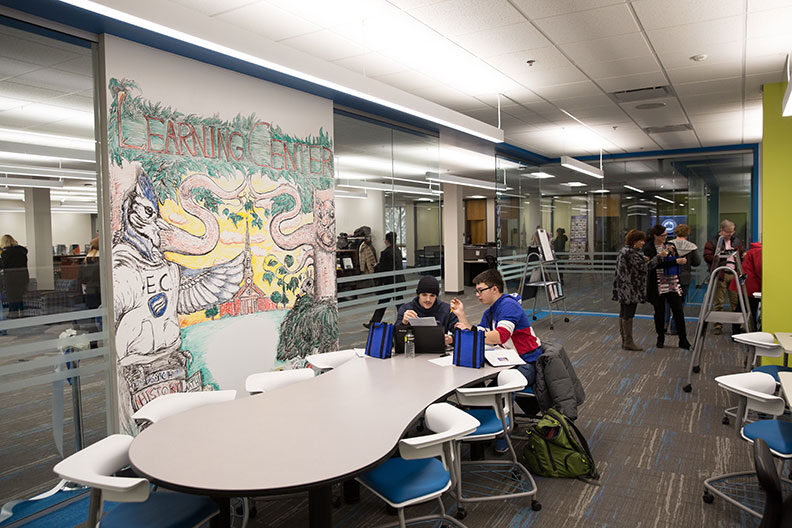 Two male students sit at a table inside the Elmhurst University Learning Center, facing a large mural of the school mascots.